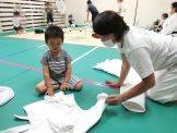 先生と3歳児が柔道衣を畳む様子