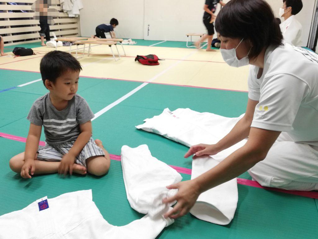 先生が3歳児に柔道衣の畳み方を教える様子